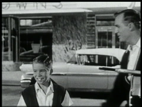 b/w 1959 boy standing on sidewalk joined by father / he points + father looks - 1959 stock videos & royalty-free footage