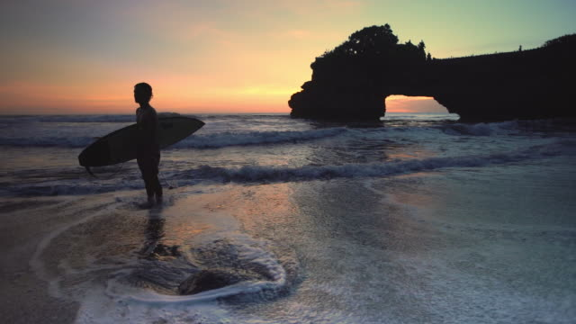 A boy standing on the beach holding a surfboard in Tanah lot Bali