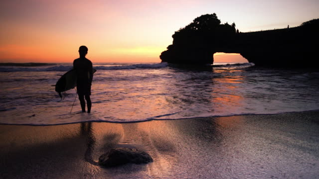 a boy standing on the beach holding a surfboard in tanah lot bali - indonesia landscape stock videos & royalty-free footage