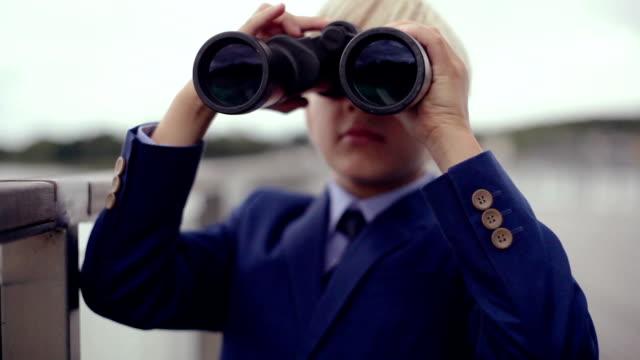 Boy (8-9) standing outdoors using binoculars, lake in background