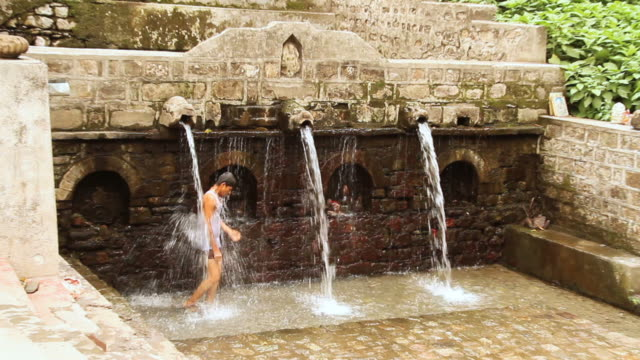 ws zi boy standing under fountain of sitabani temple at jim corbett national park  / nainital, uttarakand, india - un ragazzo adolescente video stock e b–roll