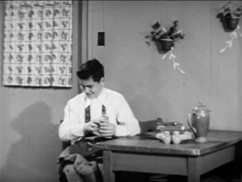 b/w 1949 boy standing up from kitchen table + talking to man + woman washing dishes in kitchen - washing up stock videos & royalty-free footage