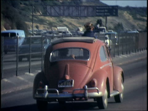 vidéos et rushes de boy standing up through sunroof of vw beetle as it drives on 405 highway - 1970