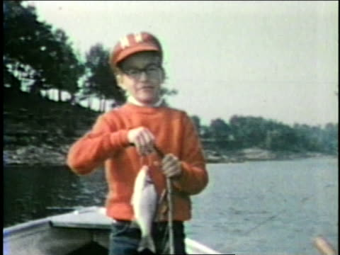 A boy stands in the bow of a small fishing boat and shows off the fish he just caught.