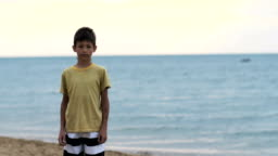 boy stands on the beach near the sea and looks at the camera
