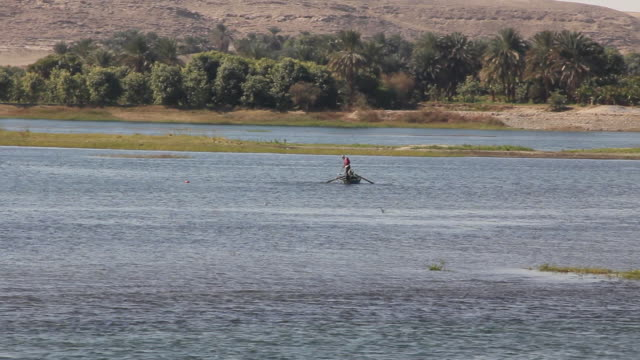 MS Boy stirring water by using paddle in fishing boat / Aswan, Egypt