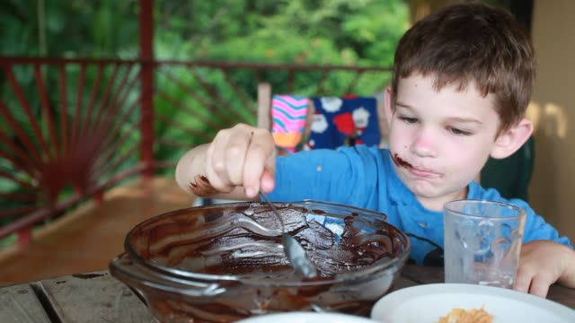 boy stirs large bowl of chocolate with spoon then uses his finger to stir the chocolate then licks the chocolate off his finger. - kelly mason videos 個影片檔及 b 捲影像