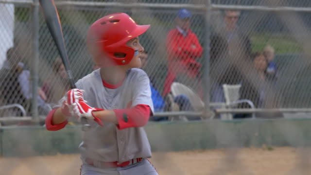 boy strikes out batting and playing little league baseball game. - slow motion - brown stock videos & royalty-free footage