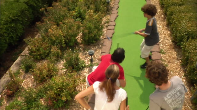 boy successfully making miniature golf shot / family jumping up and down in celebration - minigolf stock-videos und b-roll-filmmaterial
