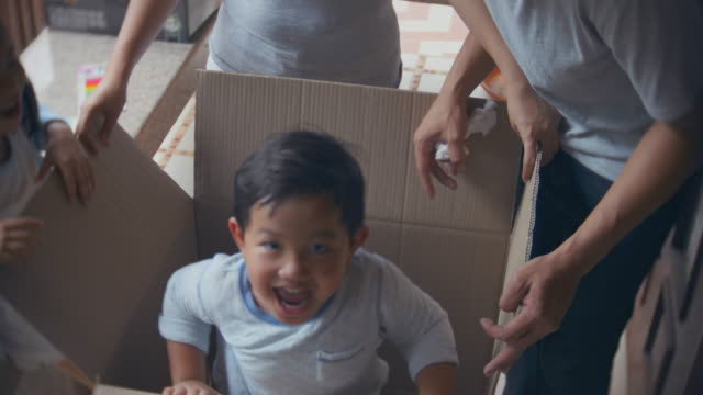 boy surprising his family by jumping out of a cardboard box - two parents stock videos & royalty-free footage