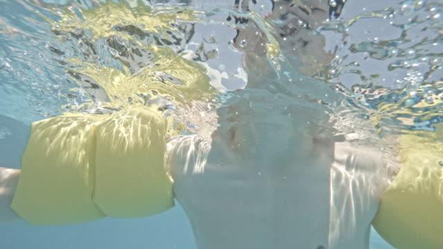 junge schwimmen im pool - schwimmflügel stock-videos und b-roll-filmmaterial