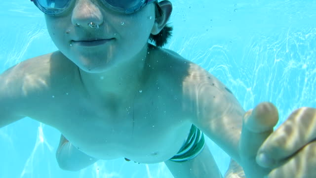 boy (10 yrs) swimming underwater and smiling to camera - 10 11 år bildbanksvideor och videomaterial från bakom kulisserna
