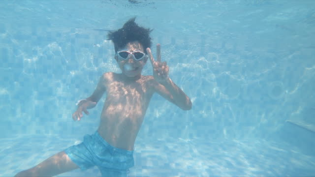 boy swimming underwater in a swimming pool - v sign stock videos & royalty-free footage