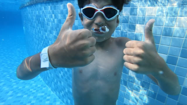 Boy swimming underwater in a swimming pool