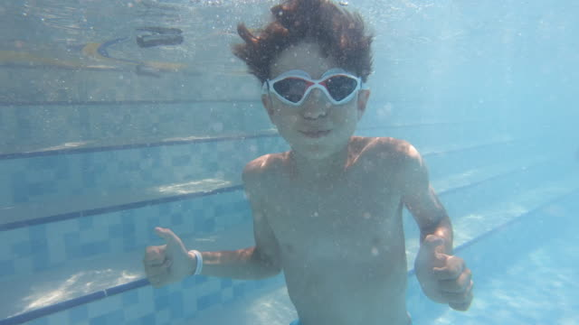 boy swimming underwater in a swimming pool - swimming goggles stock videos & royalty-free footage
