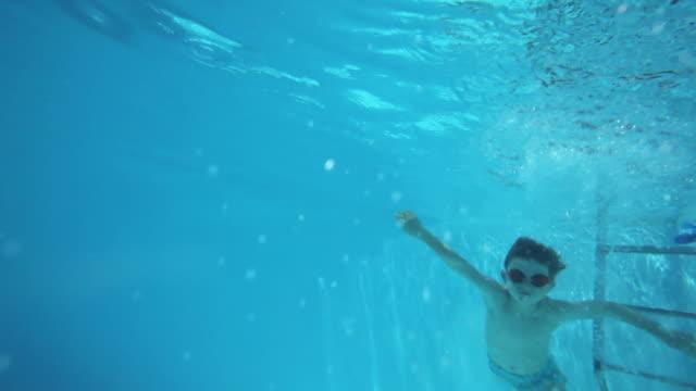 vidéos et rushes de ms boy (6-7) swimming underwater in swimming pool / fayence, var, france - var