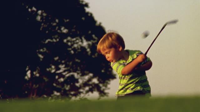 stockvideo's en b-roll-footage met sm la ms boy swinging golf club and hitting ball on golf course / minnesota, usa - golf sport