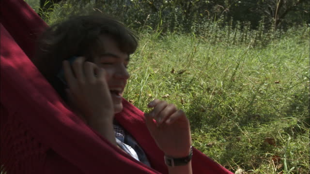cu boy (15-16) swinging in red hammock and talking on mobile phone, bouillon, belgium - one teenage boy only stock videos and b-roll footage