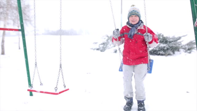 vídeos de stock e filmes b-roll de rapaz swing no parque de inverno - equipamento de parque infantil