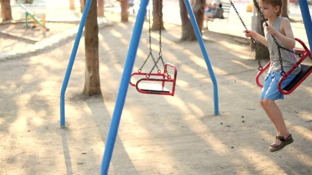 vídeos de stock, filmes e b-roll de menino balançar em um balanço no parque - reclusão