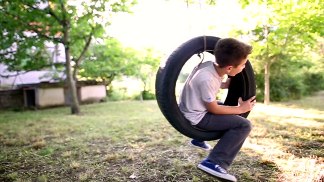 boy swinging on a tire swing - hanging stock videos & royalty-free footage