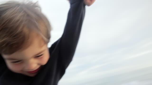 cu ts boy swinging on beach / los angeles, california, united states     - swinging stock videos & royalty-free footage