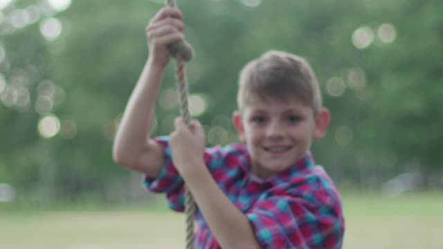 boy swinging on rope outdoors - tyre swing stock videos & royalty-free footage