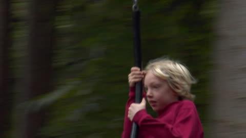 ms swish pan boy (8-9) swinging on rope swing between trees / norwich, norfolk, united kingdom - swish pan stock videos & royalty-free footage