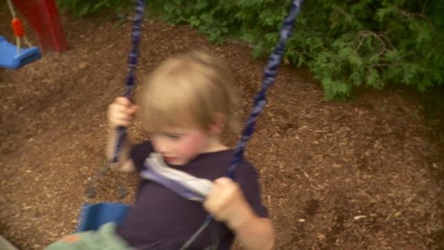vídeos y material grabado en eventos de stock de ms slo mo pan boy (4-5) swinging on swing in playground / stowe, vermont, usa - columpiarse