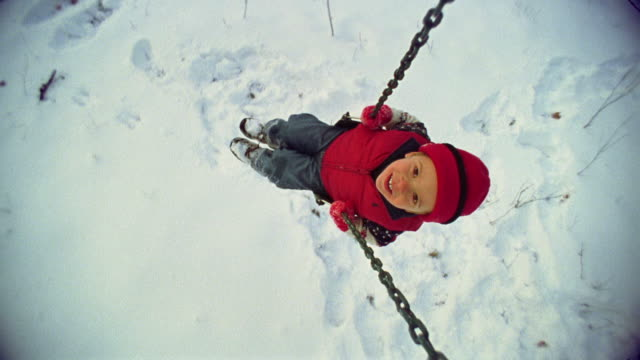 oh ws boy swinging on swing in winter / minnesota, usa - mitten stock videos and b-roll footage