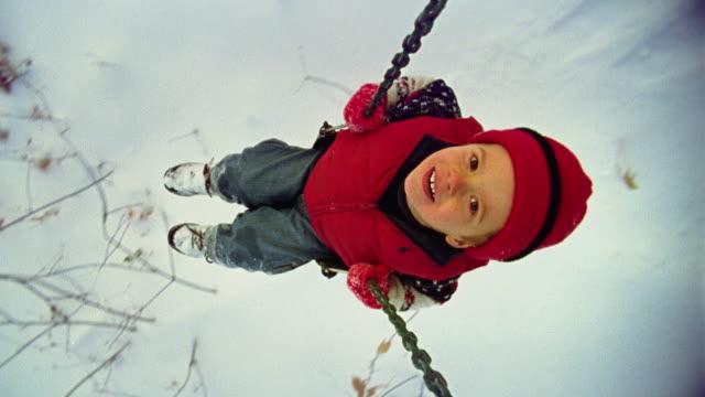 OH WS Boy swinging on swing in winter / Minnesota, USA