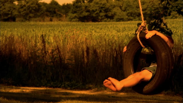 a boy swings on a tire swing  by a grassy field. - tyre swing stock videos & royalty-free footage