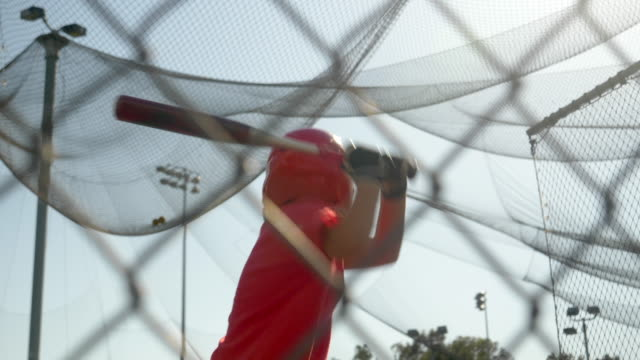vídeos y material grabado en eventos de stock de a boy swings the bat and practices little league baseball at the batting cages. - slow motion - bate de béisbol