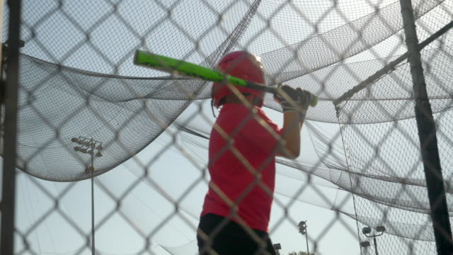 a boy swings the bat and practices little league baseball at the batting cages. - slow motion - little league stock videos and b-roll footage