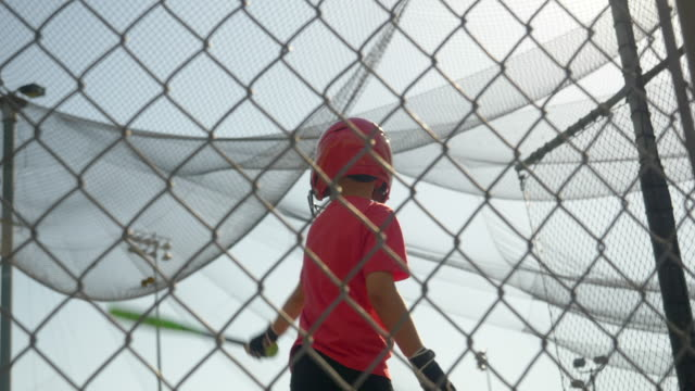 a boy swings the bat and practices little league baseball at the batting cages. - slow motion - gabbia di battuta video stock e b–roll