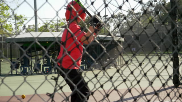 a boy swings the bat and practices little league baseball at the batting cages. - gabbia di battuta video stock e b–roll