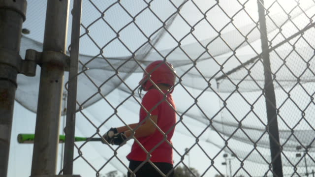 a boy swings the bat and practices little league baseball at the batting cages. - slow motion - filmed at 180 fps - gabbia di battuta video stock e b–roll