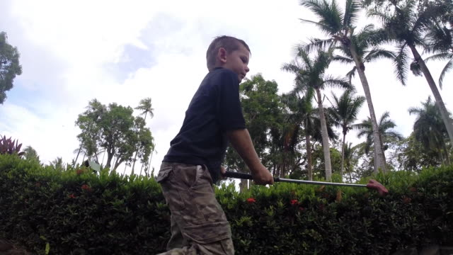 boy takes 2 shots to sink his ball on a mini golf course and fails. - kelly mason videos stock-videos und b-roll-filmmaterial