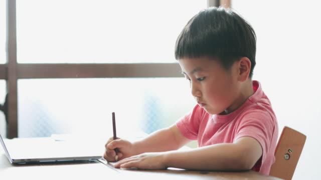 vídeos de stock e filmes b-roll de boy taking an e-learning course at home - workshop