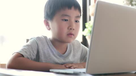 vídeos y material grabado en eventos de stock de niño tomando un curso de e-learning en casa - vida sencilla