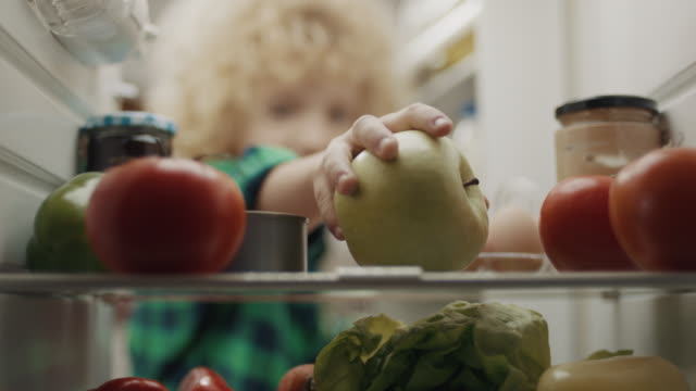 vidéos et rushes de garçon prenant la pomme du réfrigérateur ! - pomme