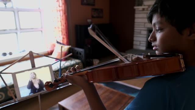 vidéos et rushes de boy taking music lesson over video conferencing - musicien