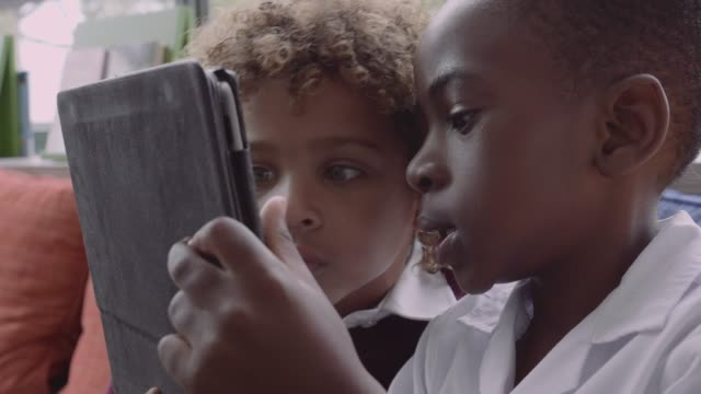 vidéos et rushes de boy taking selfie with friend in school - utiliser une tablette numérique