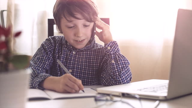 Boy talking on cell phone and writing notes