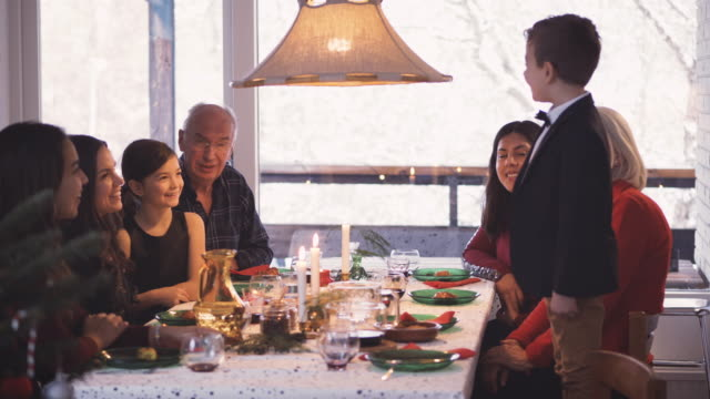 boy talking to family while standing on chair during christmas meal at table - kerzenschein stock-videos und b-roll-filmmaterial