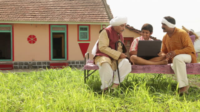 boy teaching laptop to his father and grandfather  - dhoti video stock e b–roll