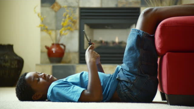 ms boy (10-11) text messaging, laying on living room floor / bothell, washington state, usa - piedi alzati video stock e b–roll