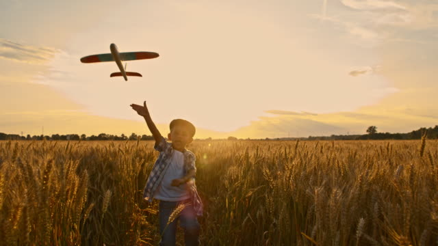 slo mo boy throwing an airplane - wheat stock videos & royalty-free footage