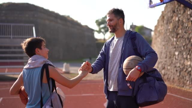 バスケットボールのトレーニングの後、コーチにハイファイブを投げる少年 - 完了する点の映像素材/bロール