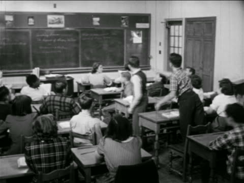 B/W 1951 REAR VIEW boy throwing paper airplane in classroom / second boy retrieves it